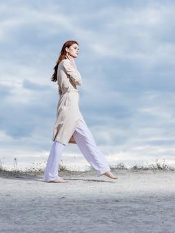 Eine frau, die leichte kleidung trägt, geht auf sand in der natur und wolken im hintergrund.