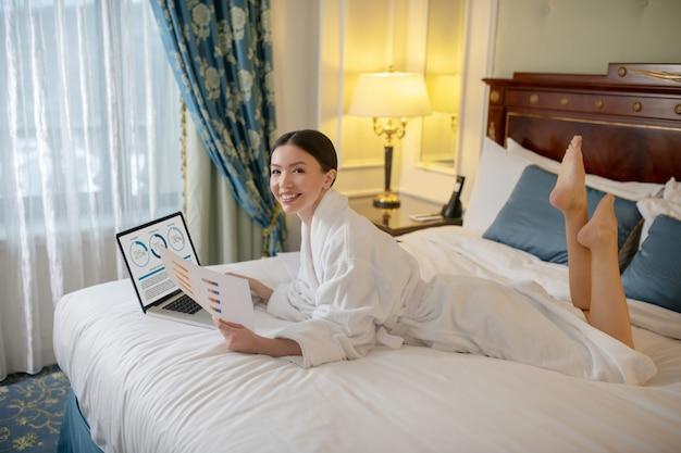 Eine frau, die mit einem geschäftsbericht in ihrem schlafzimmer arbeitet