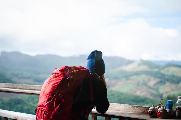 Eine frau, die mit einem rucksack reist, sitzt, beobachtet und genießt die schöne natur. das ist ihr urlaub