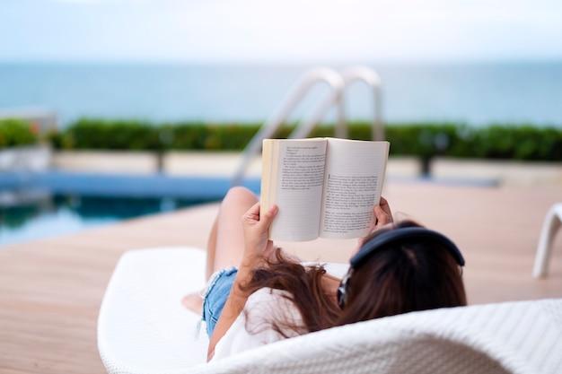 Eine frau, die mit kopfhörer musik hört und ein buch liest, während sie sich am pool hinlegt