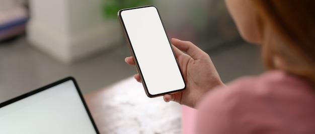 Eine frau, die modell-smartphone verwendet, um sich zu entspannen, während sie mit modell-laptop auf holztisch arbeitet