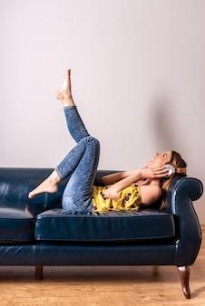 Eine frau, die musik hört, während sie auf einem sofa posiert