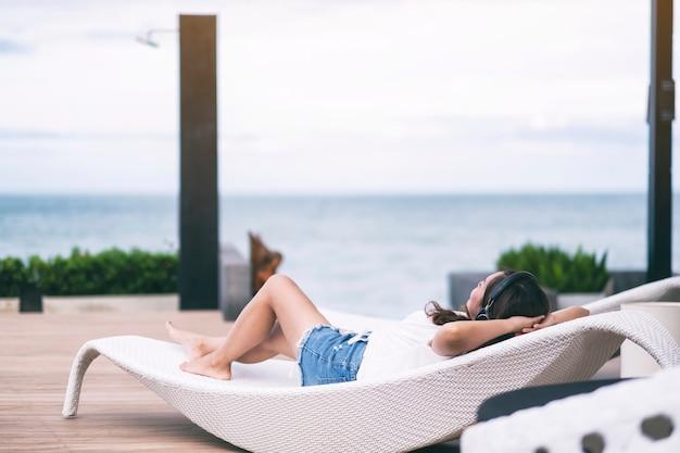 Eine frau, die musik mit kopfhörer hört, während sie sich am swimmingpool hinlegt