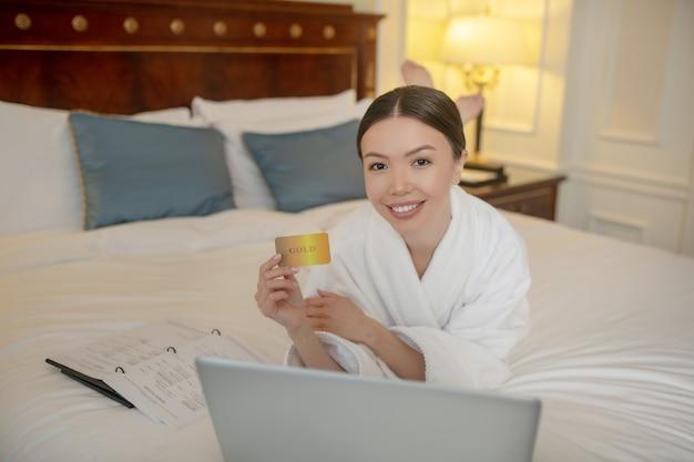 Eine frau, die online-zahlung mit der goldkreditkarte macht