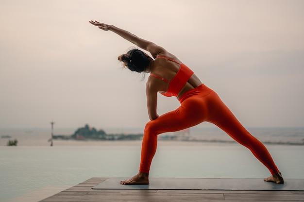 Eine frau, die orangefarbene sportkleidung trägt, macht utthita parsvakonasana extended side angle pose