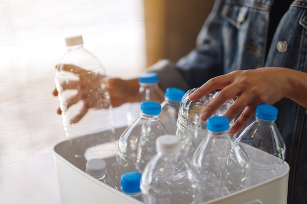 Eine frau, die recycelbare plastikmüllflaschen sammelt und in einen mülleimer zu hause trennt