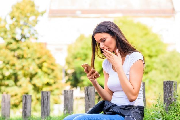 Eine frau, die schlechte nachrichten auf ihrem smartphone erhält