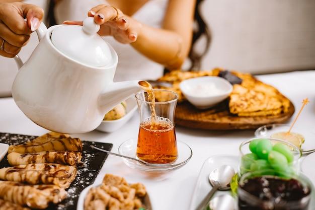 Eine frau, die schwarzen tee von der weißen keramik-teekanne in die seitenansicht des armudu-glases gießt