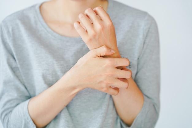 Eine frau, die sich am arm kratzt und eine allergische reaktion hat oder von einem insekt gestochen wird