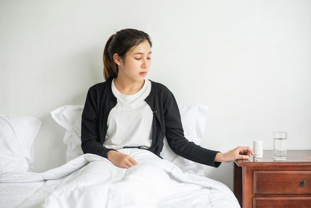 Eine frau, die sich auf der couch unwohl fühlt und im begriff ist, antibiotika einzunehmen.