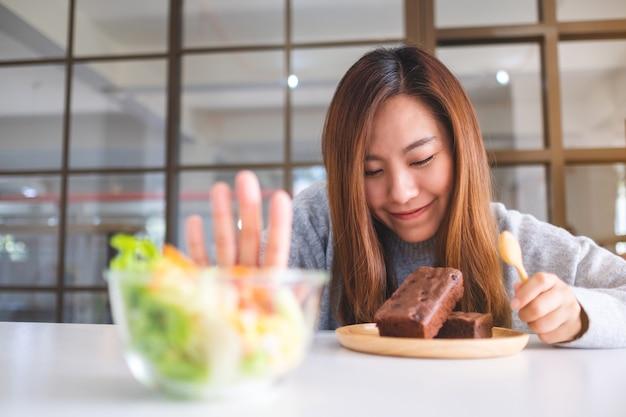 Eine frau, die sich entscheidet, brownie-kuchen zu essen und ein handzeichen macht, um einen gemüsesalat auf dem tisch abzulehnen?