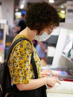 Eine frau, die sich in einer buchhandlung bücher ansieht, trägt eine gesichtsmaske, die sie vor viren schützt