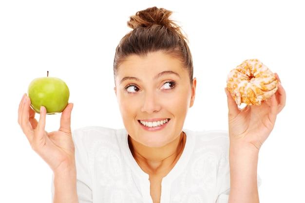 Eine frau, die sich zwischen apfel und donut entscheidet