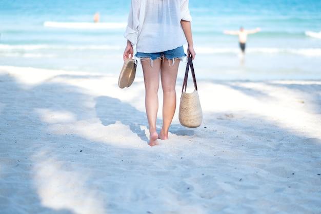 Eine frau, die tasche und schuhe hält, während am strand mit dem hintergrund des meeres und des blauen himmels spazieren geht