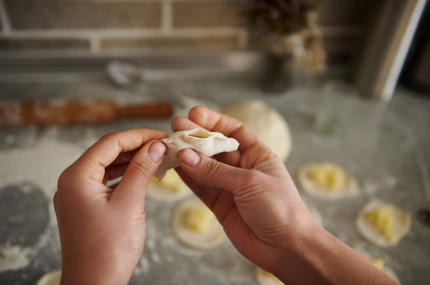 Eine frau, die traditionelle knödel (vareniki oder ravioli) macht. hände im fokus