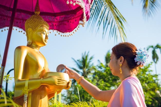 Eine frau, die traditionelle thailändische kleider trägt, gießt anlässlich des songkran-festivaltages wasser in die buddha-statue