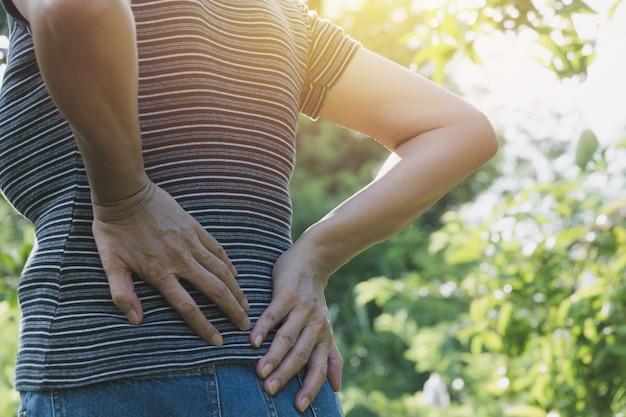 Eine frau, die unter rückenschmerzen-, rückenmarksverletzungs- und muskelproblemproblem am im freien leidet.
