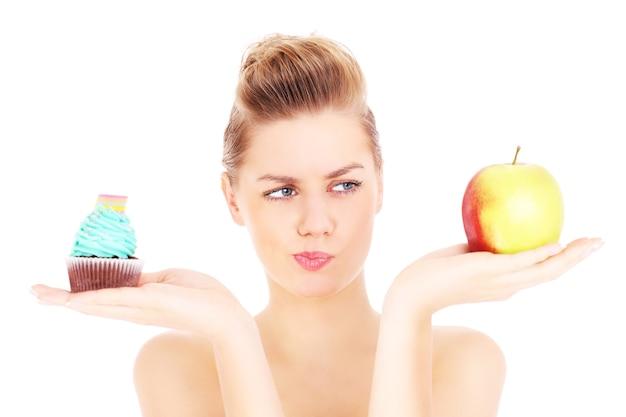 Eine frau, die versucht, eine entscheidung zwischen cupcake und apfel auf weißem hintergrund zu treffen