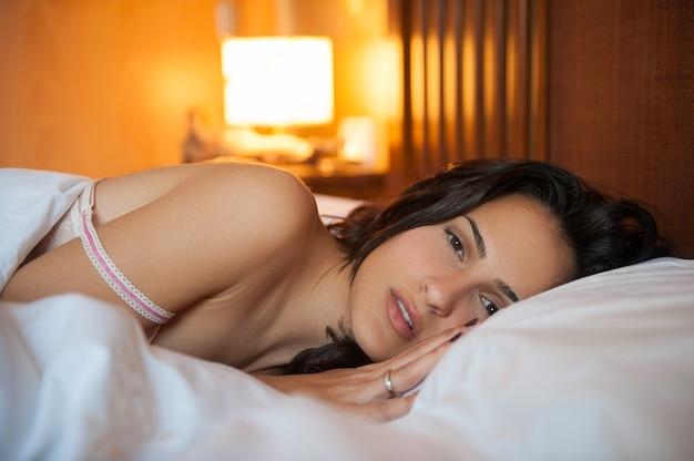 Eine frau, die von ihrem bett aus vor der kamera zusieht, kurz vor dem einschlafen