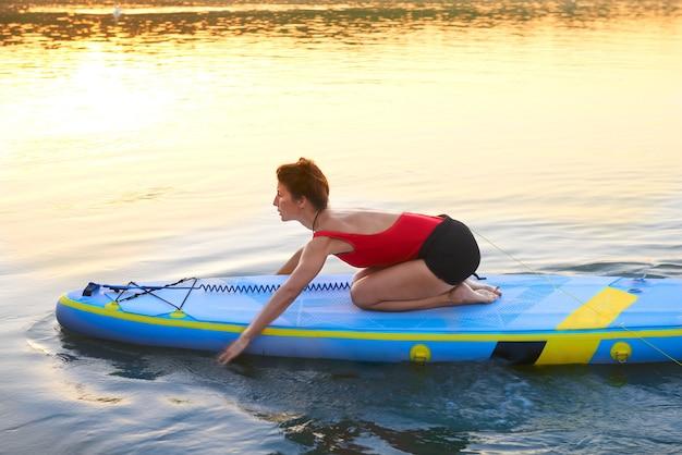 Eine frau, die während des schönen morgens auf einem fluss paddelt
