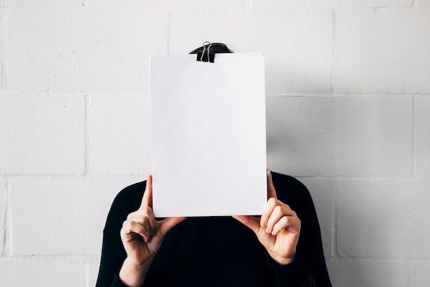 Eine frau, die weißbuch vor ihrem gesicht gegen weiße wand hält