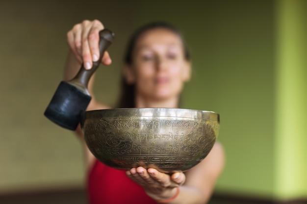 Eine frau, die yoga praktiziert, führt im studio mit einer metallschale klangmeditation durch