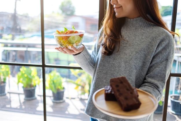 Eine frau, die zwischen einem teller brownie-kuchen und einer schüssel gemüsesalat hält und essen auswählt