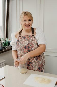 Eine frau drückt zitronensaft mit der hand in den mixbecher in der küche.