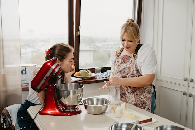 Eine frau drückt zitronensaft mit der hand in den mixbecher neben ihrer hübschen freundin in der küche.