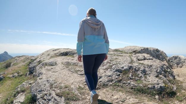 Eine frau erklimmt eine klippe und eröffnet den blick auf das grenzenlose blaue meer. sie bleibt stehen und breitet die arme seitlich aus, genießt die schöne landschaft und die frische seeluft. 4k uhd
