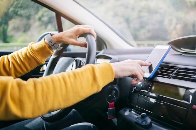Eine frau fährt ein auto, während sie das handy mit der hand benutzt