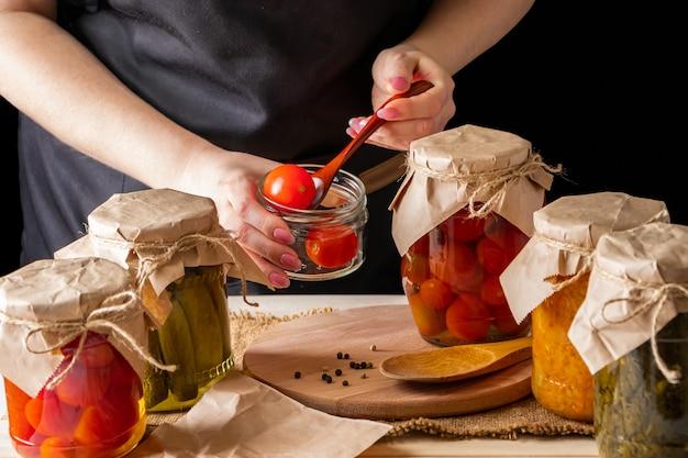 Eine frau fermentiert gemüse. eingelegte tomaten in gläsern.