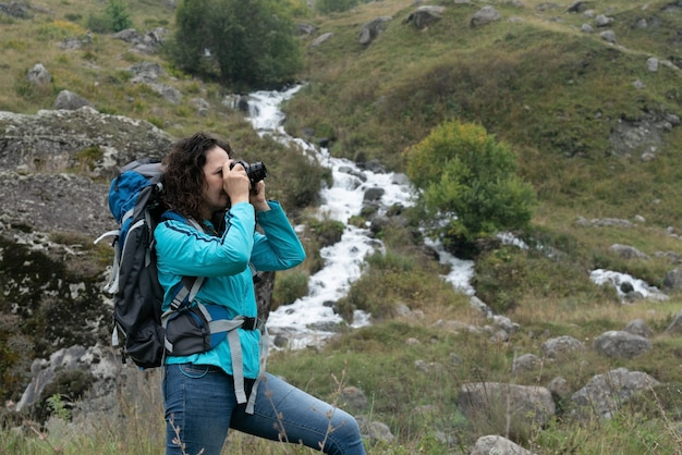 Eine frau fotografiert die landschaft in den bergen.