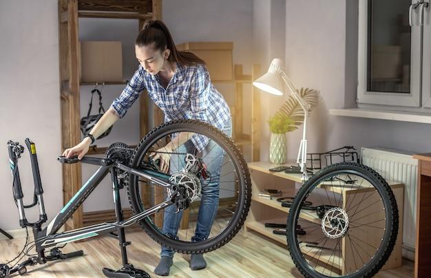 Eine frau führt wartungsarbeiten an seinem mountainbike durch. konzept zur befestigung und vorbereitung des fahrrads für die neue saison