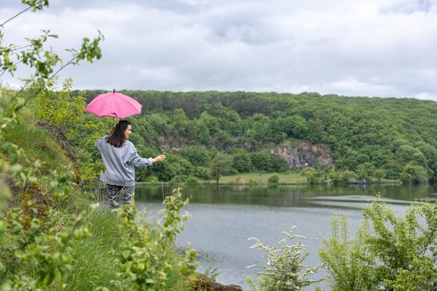 Eine frau geht bei bewölktem wetter unter einem regenschirm in einer bergigen gegend spazieren