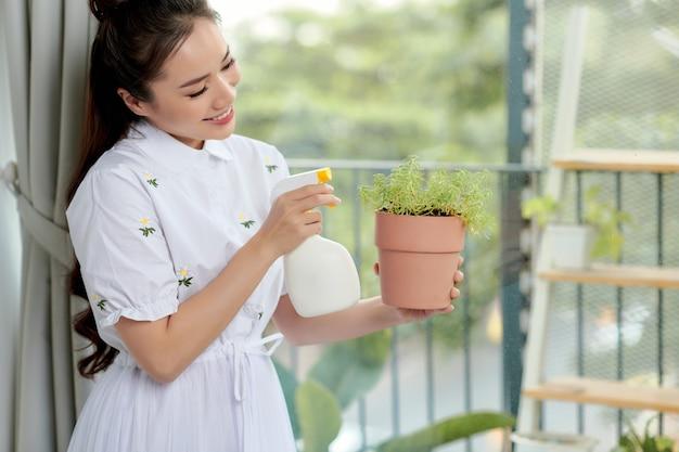 Eine frau gießt und sprüht heimische pflanzen. konzept des hausgartens. frühlingszeit. pflege der heimischen pflanzen.