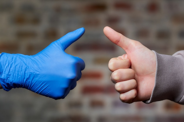 Eine frau greift mit einem einweghandschuh zu einem mann, der auch ihre daumen mit nackter hand aufgibt.