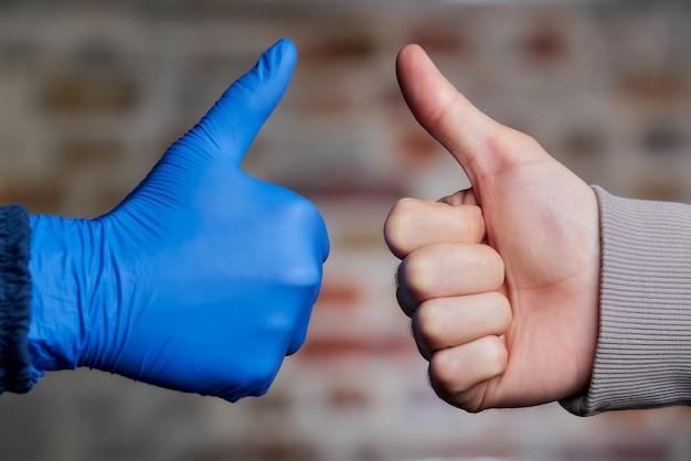 Eine frau greift mit einem medizinischen einweghandschuh zu einem mann, der auch ihre daumen mit nackter hand aufgibt.