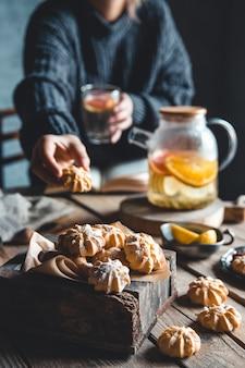 Eine frau greift nach einem kuchen und trinkt grapefruitee. gesundes getränk.