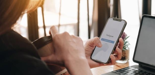 Eine frau hält apple iphone 12 mit instagram-anwendung auf dem bildschirm im café.