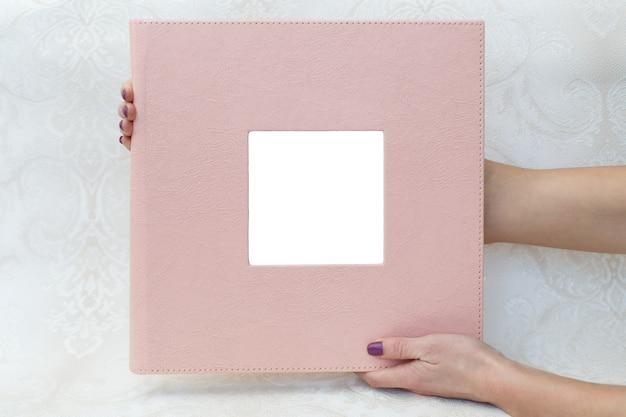 Eine frau hält ein familienfotobuch mit schild. die person schaut auf das fotobuch. beispiel rosa fotoalbum mit ohoto-prägung. hochzeitsfotoalbum mit lederbezug.