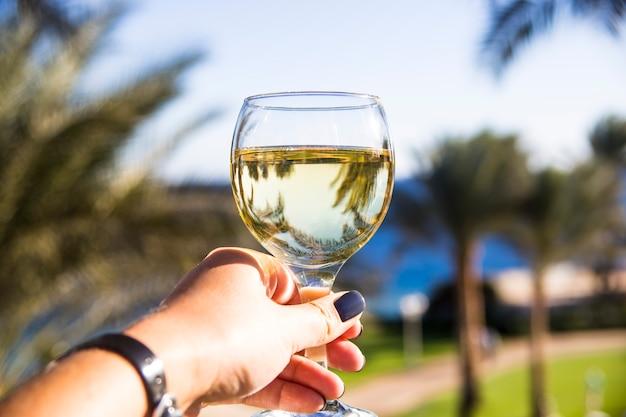 Eine frau hält ein glas wein in der hand und steht zwischen palmen am meer