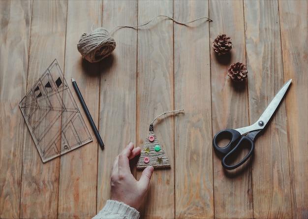 Eine frau hält ein handgemachtes weihnachtsbaumspielzeug in der hand. konzept von weihnachten diy. draufsicht