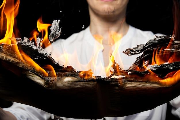 Eine frau hält eine brennende zeitung, gefälschtes nachrichtenkonzept.
