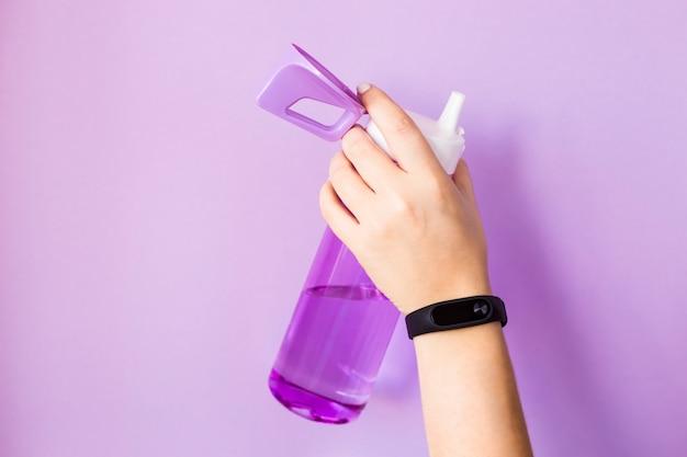 Eine frau hält eine purpurrote wasserflasche in der hand für sport. mit einem fitnessarmband am arm. auf hellem violettem hintergrund. gesunder lebensstil und fitness-konzept