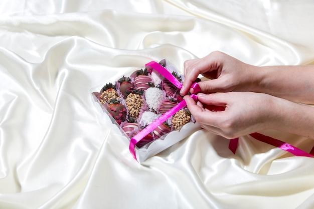 Eine frau hält eine schachtel erdbeeren mit schokoladenüberzug