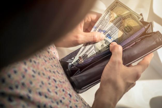Eine frau hält einen geldbeutel mit geld, dollar.