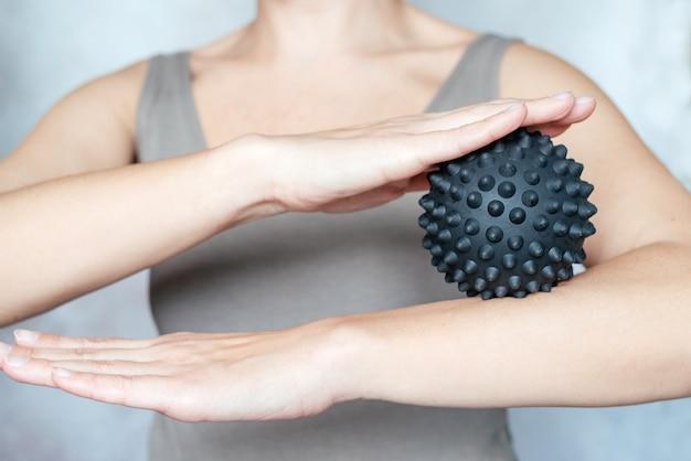 Eine frau hält einen stacheligen triggerpunkt-massageball, der zur linderung von muskelschmerzen verwendet wird