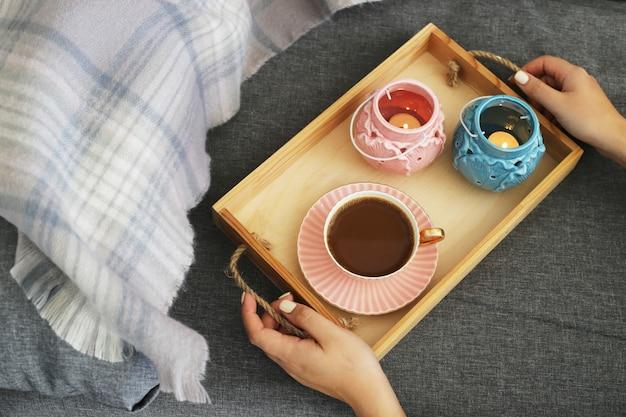 Eine frau hält einen tasse kaffee und milch auf einem hölzernen tablett