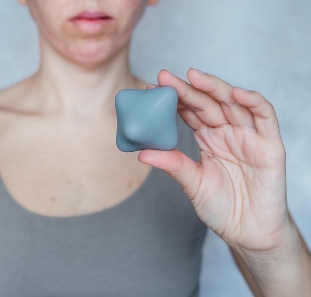 Eine frau hält einen triggerpunkt-massageball, der gegen muskelschmerzen eingesetzt wird